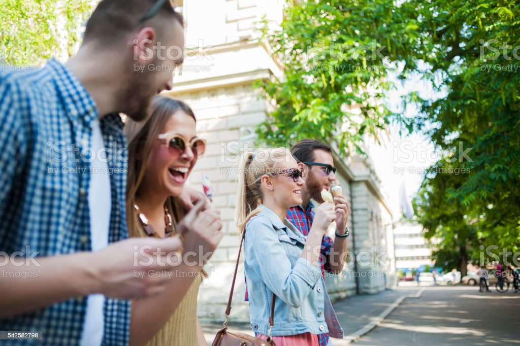 Cheerful friends eating ice cream and walking stock photo