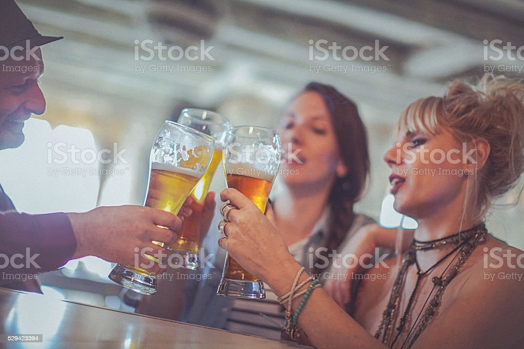 Cheerful friends enjoying time drinking beer together in bar stock photo