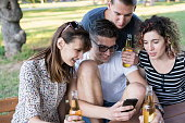 Cheerful friends hanging out at the park using smart phone