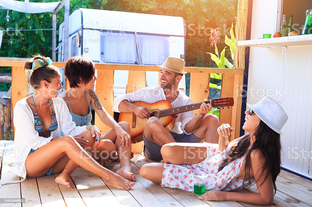 Cheerful friends having fun together on wooden veranda stock photo