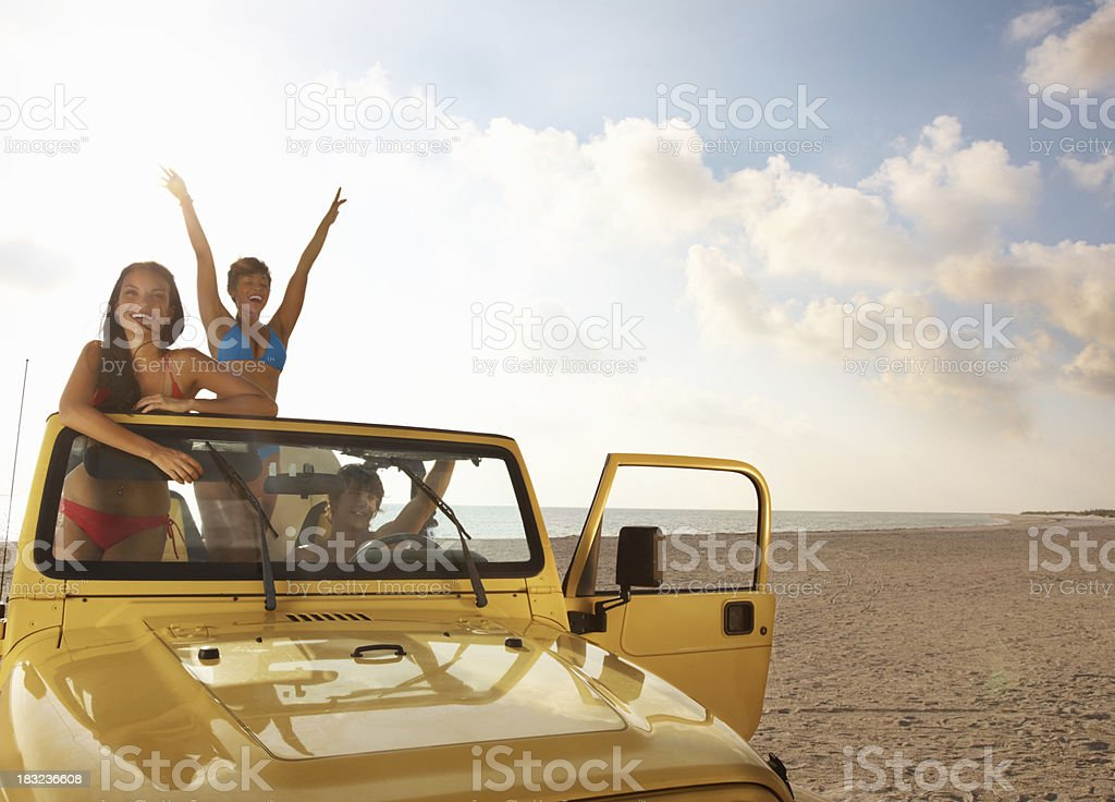 Cheerful friends in jeep having fun on the beach stock photo