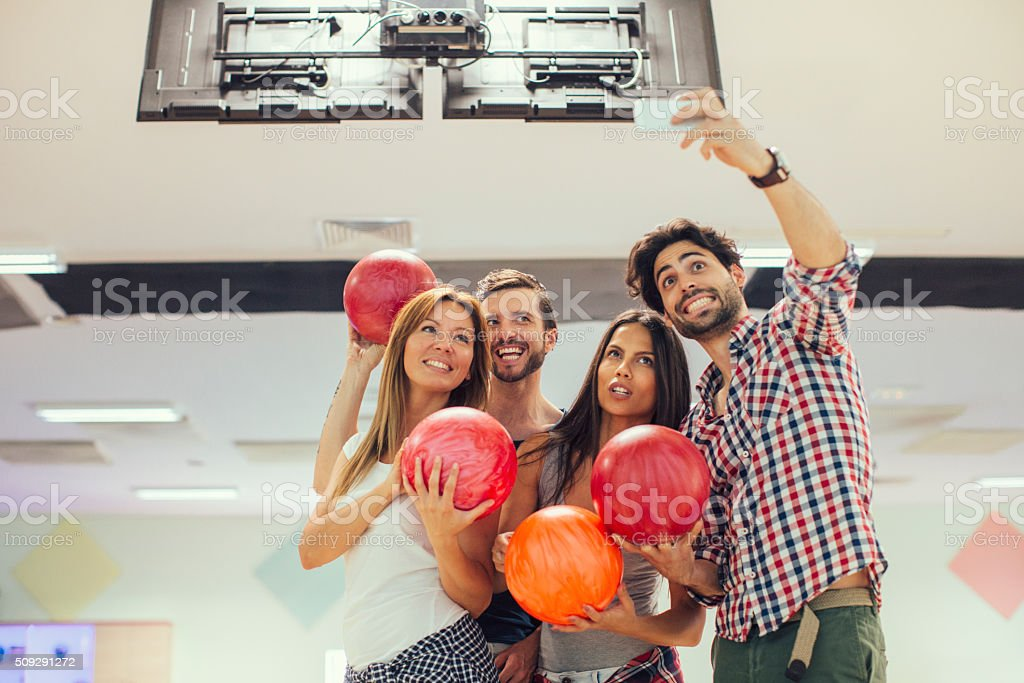 Cheerful Friends making a selfie on bowling stock photo