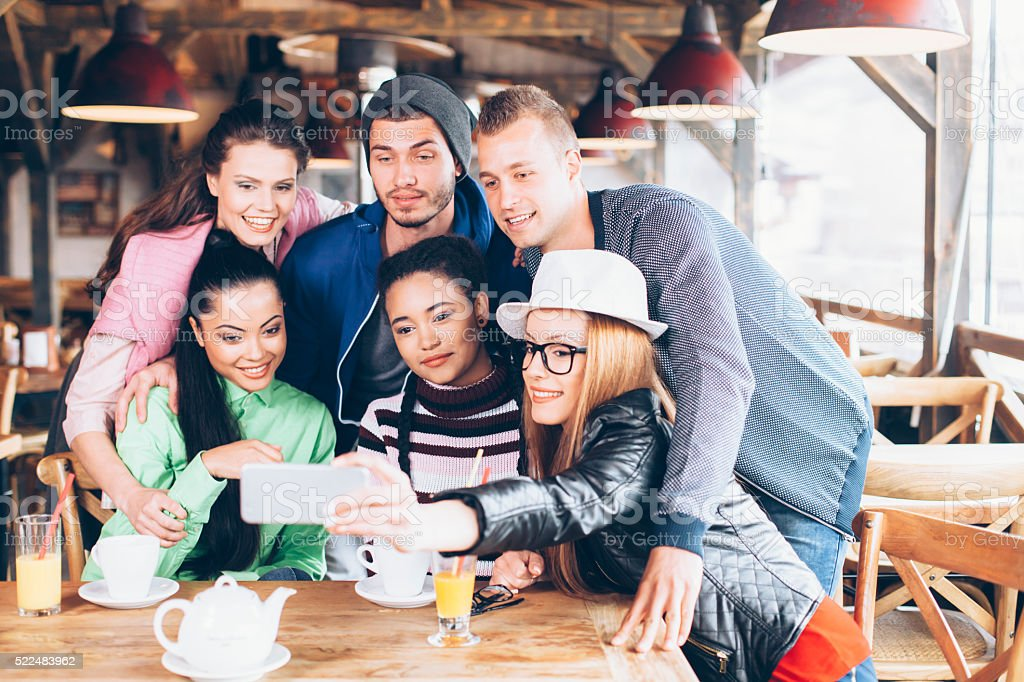 Cheerful friends making selfie at coffee shop stock photo