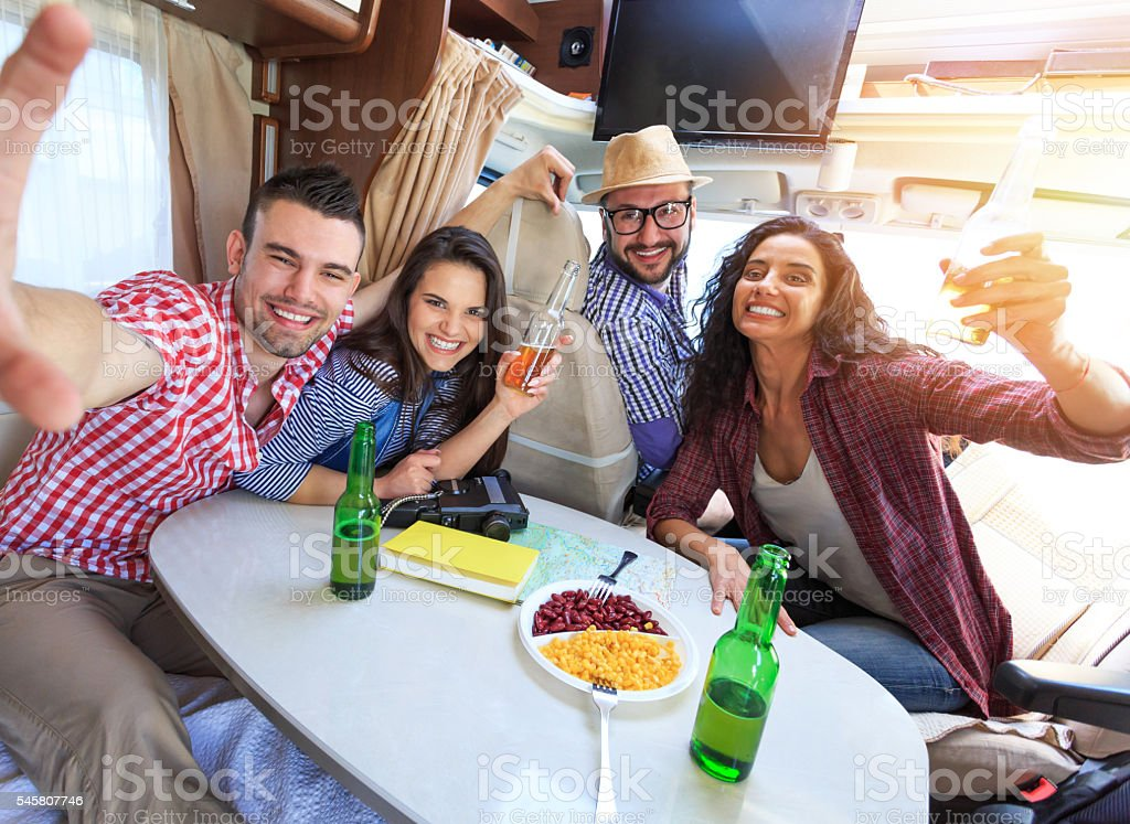 Cheerful friends making selfie inside of a camper van stock photo