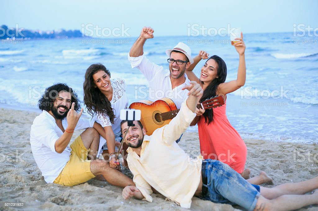 Cheerful friends making selfie on beach with monopod stock photo