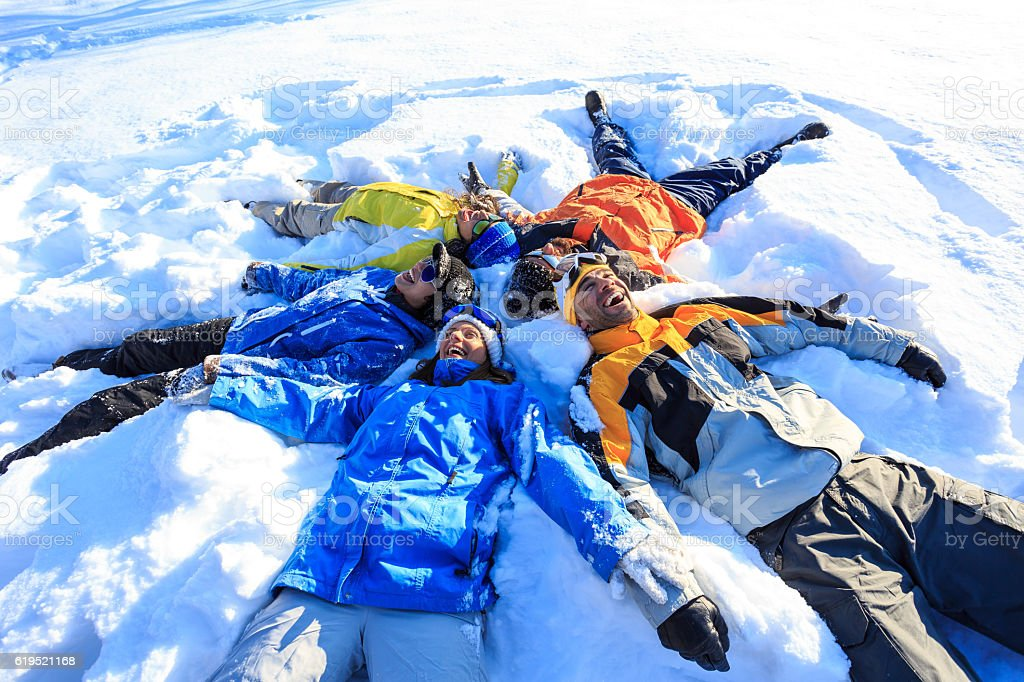 Cheerful friends making snow angels stock photo