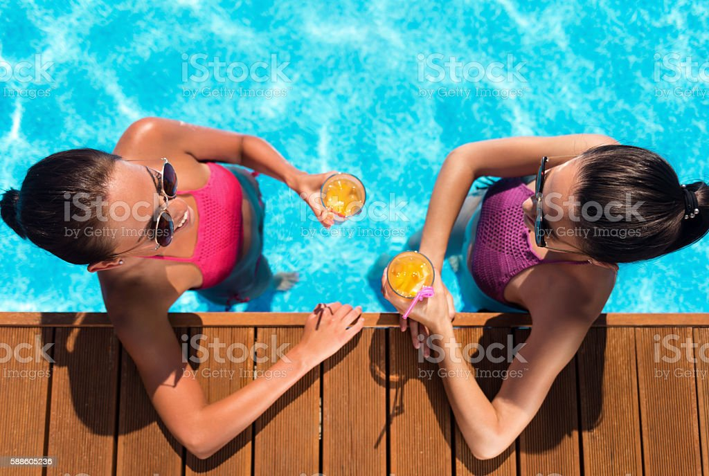 Cheerful friends resting in a swimming pool stock photo