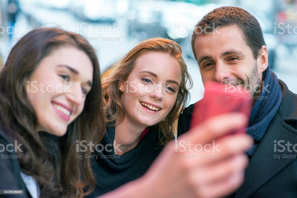 Cheerful friends taking selfie in a cafe stock photo