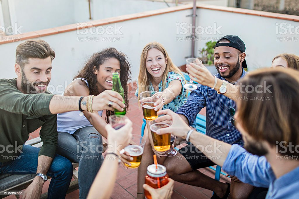Cheerful friends toasting drinks on terrace stock photo