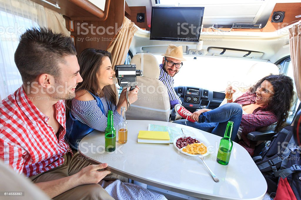Cheerful friends using vintage video camera inside camper stock photo