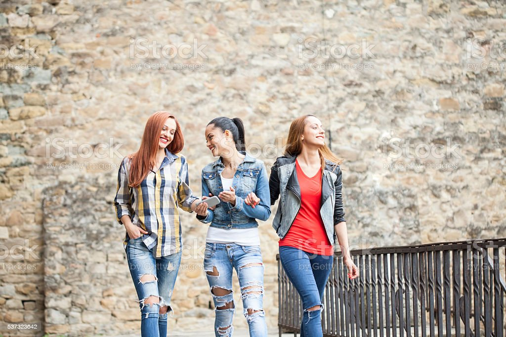 Cheerful friends walking together in the city stock photo