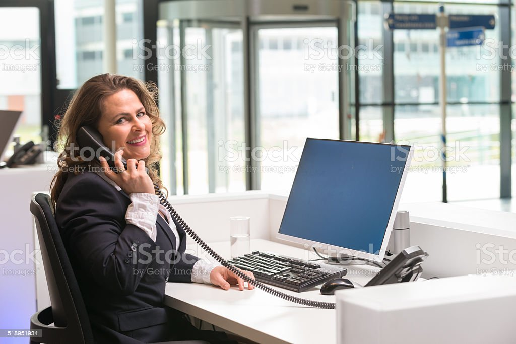 Cheerful front desk lady doing her job with passion stock photo