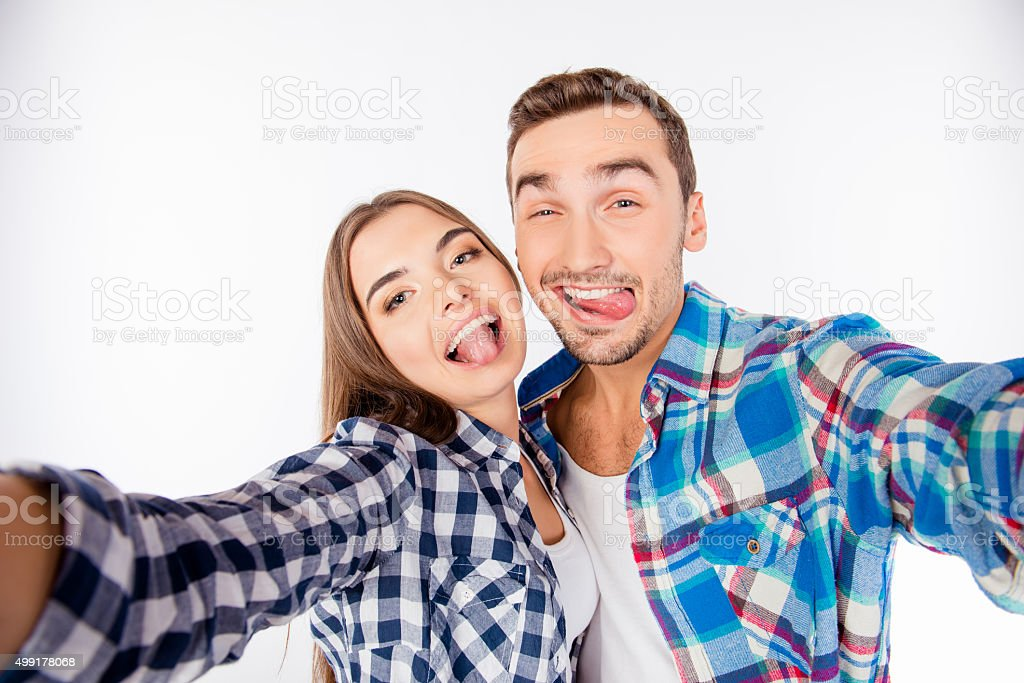 Cheerful funny couple in love making selfie photo showing tongue stock photo