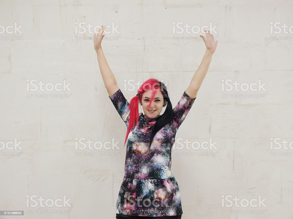 Cheerful girl against a white wall stock photo