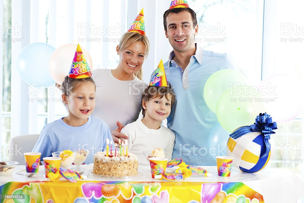 Cheerful girl celebrating birthday with brother and parents. royalty-free stock photo
