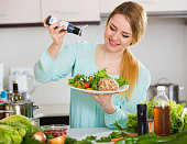 Cheerful girl in blouse adding sauce in salad with cheese