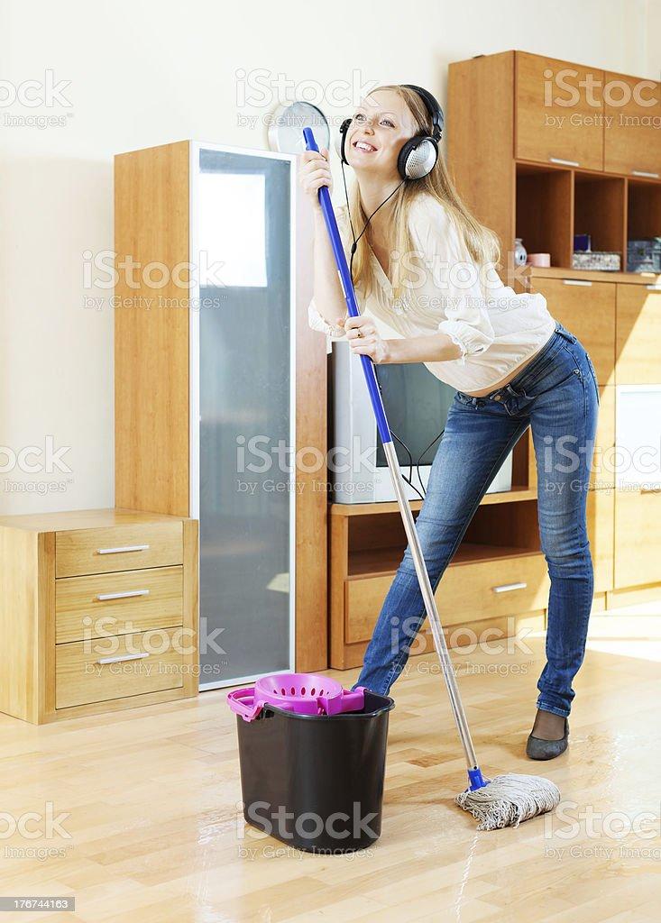 cheerful girl in headphones washing floor stock photo
