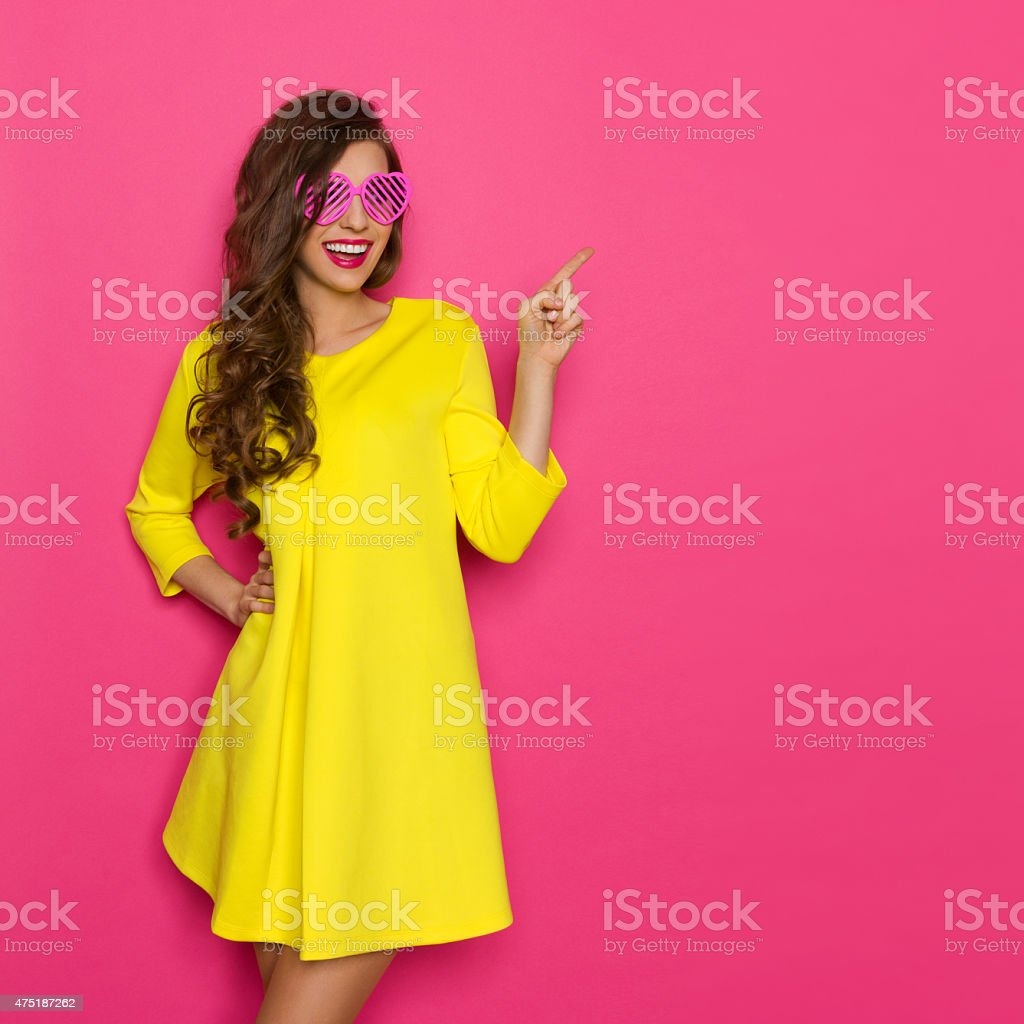 Cheerful Girl In Pink Sunglasses Pointing stock photo