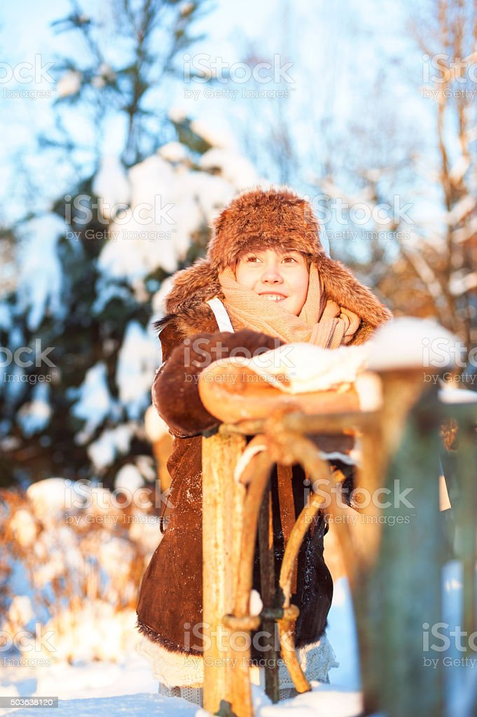 Cheerful girl in warm clothes peeking contemplating sunny winter day. stock photo