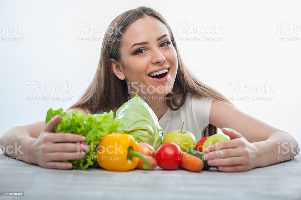 Cheerful girl is sitting with healthy food stock photo