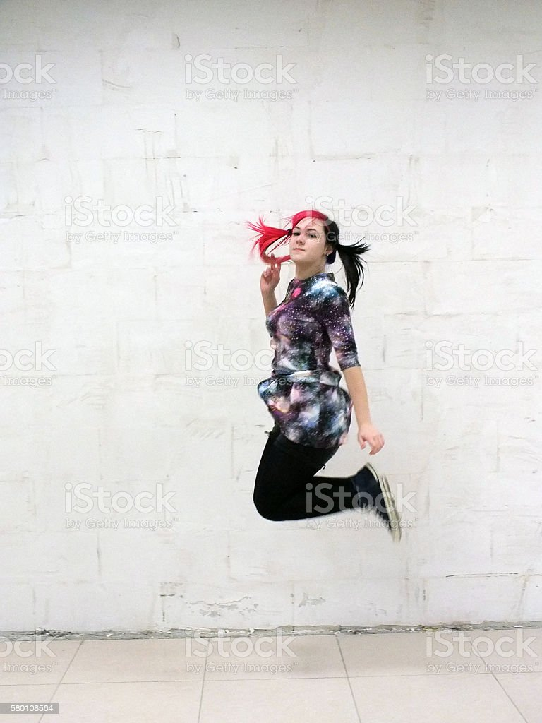 Cheerful girl jumping against a white wall stock photo