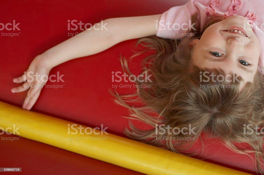 Cheerful Girl Lying In Bouncy Castle stock photo