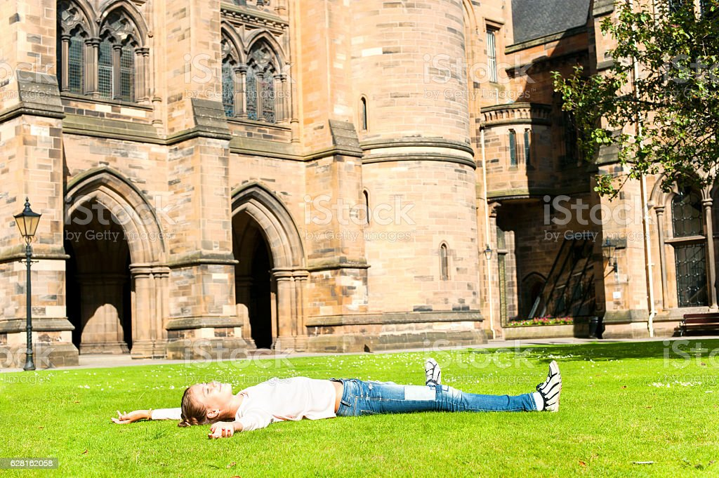 Cheerful girl lying on the grass  in Glasgow University garden. stock photo