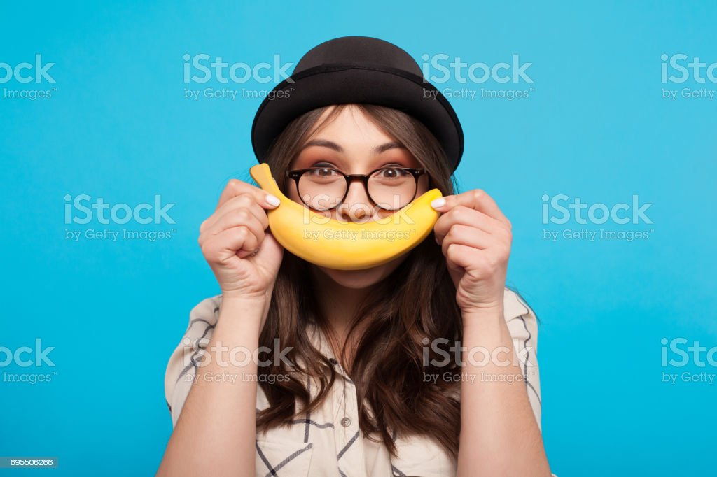 Cheerful girl posing with banana stock photo
