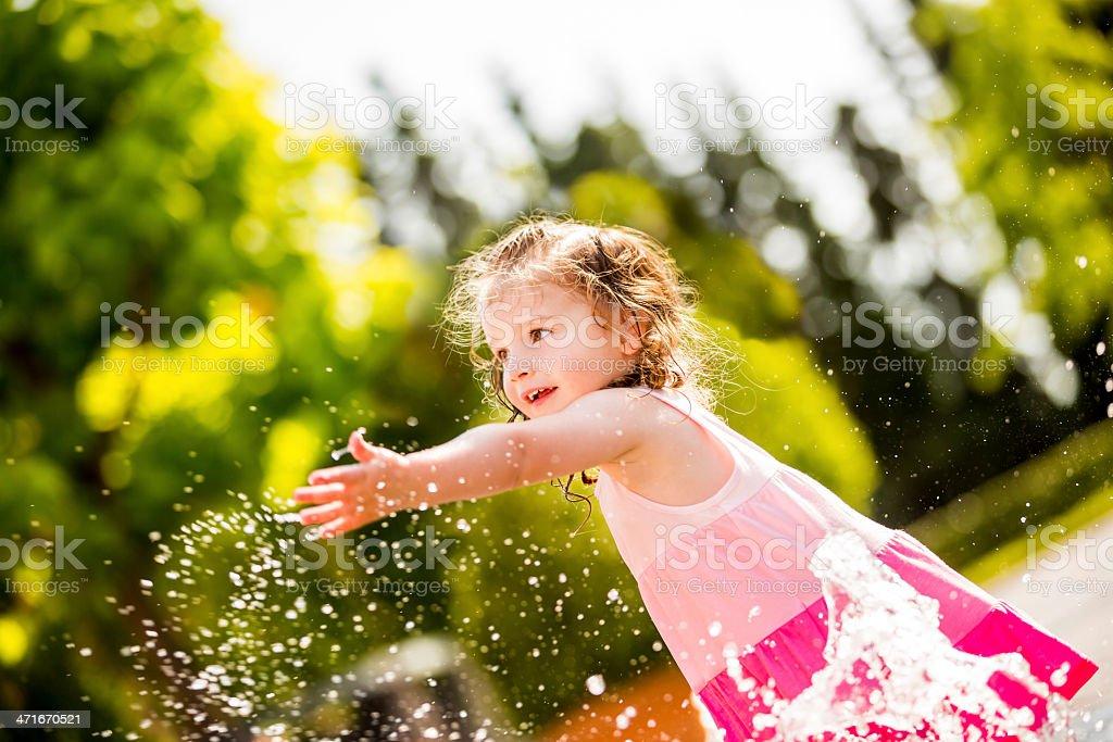 Cheerful girl splashing water with hand stock photo