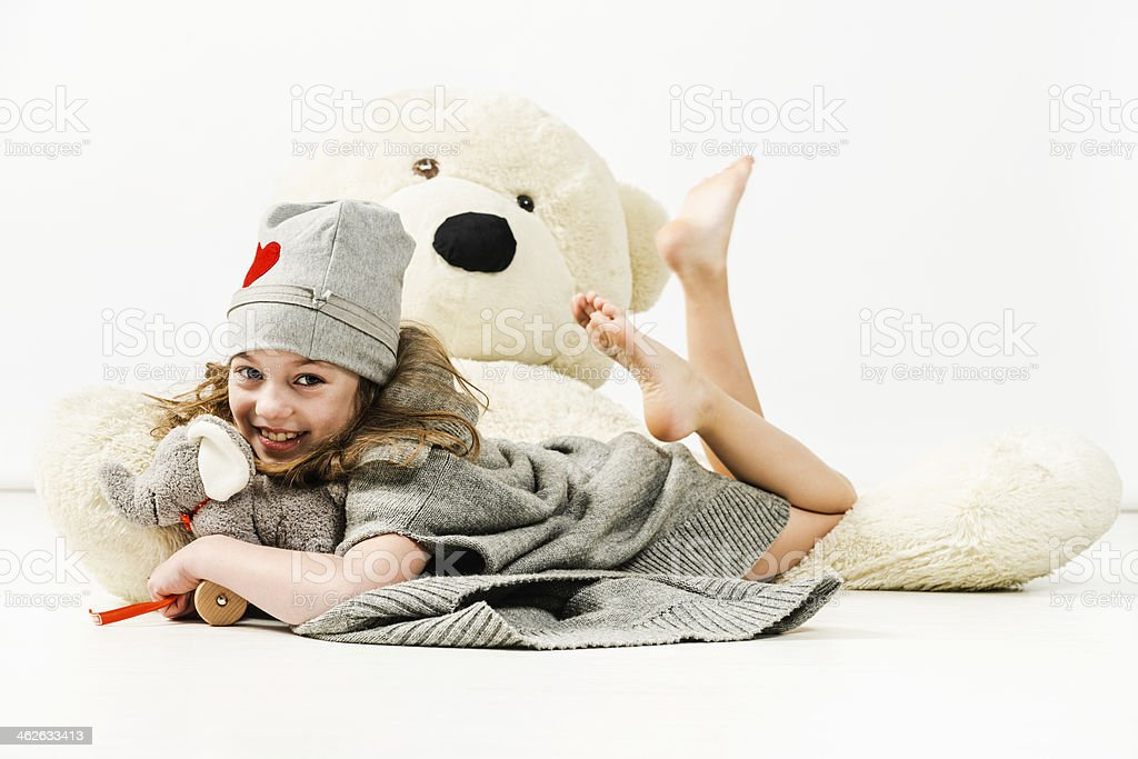 Cheerful girl with elephant toy lying on large teddy bear royalty-free stock photo