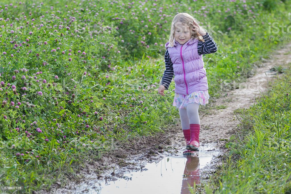 Cheerful girl with loose hair walking on dirt rain puddle stock photo