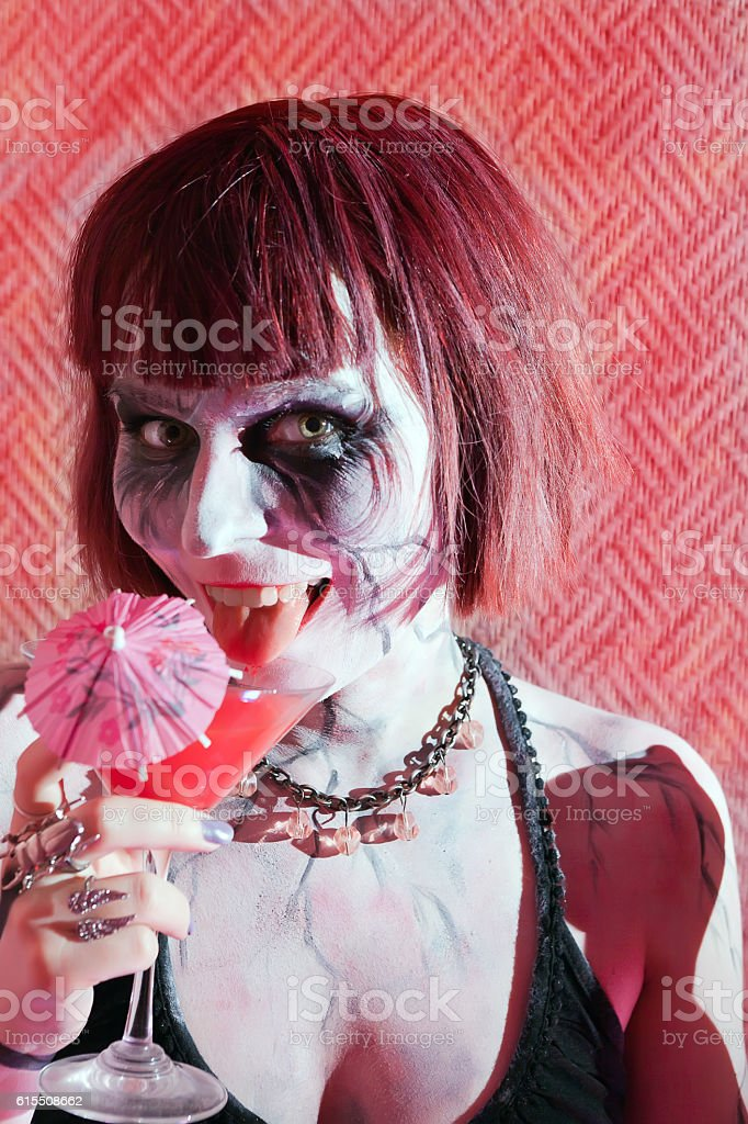 cheerful girl zombie with glass of red drink stock photo