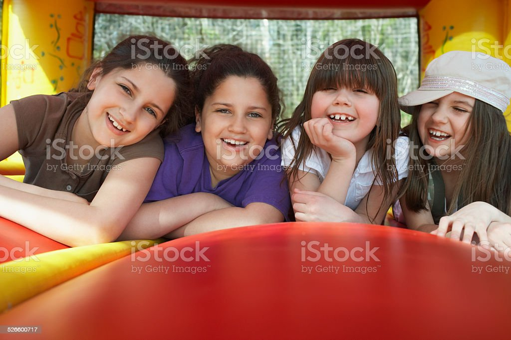 Cheerful Girls Lying In Bouncy Castle stock photo