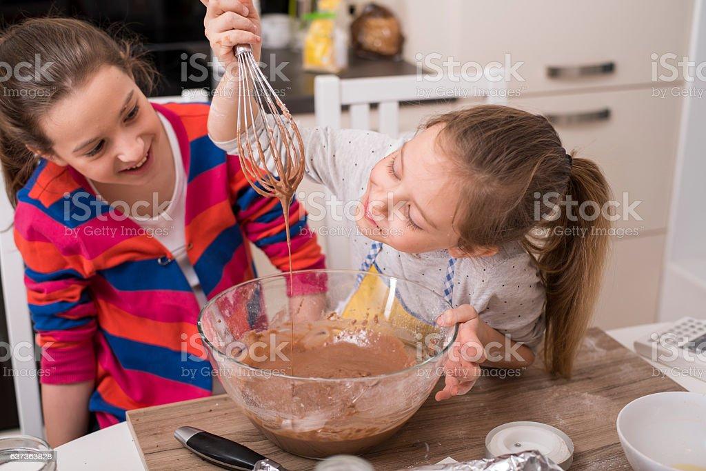 Cheerful girls making muffins stock photo
