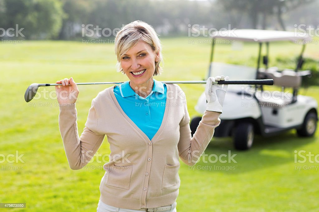 Cheerful golfer standing on the putting green stock photo