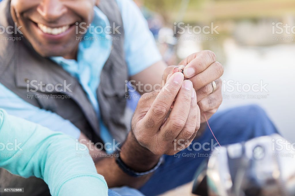 Cheerful grandfather teaches his granddaughter to bait a hook stock photo