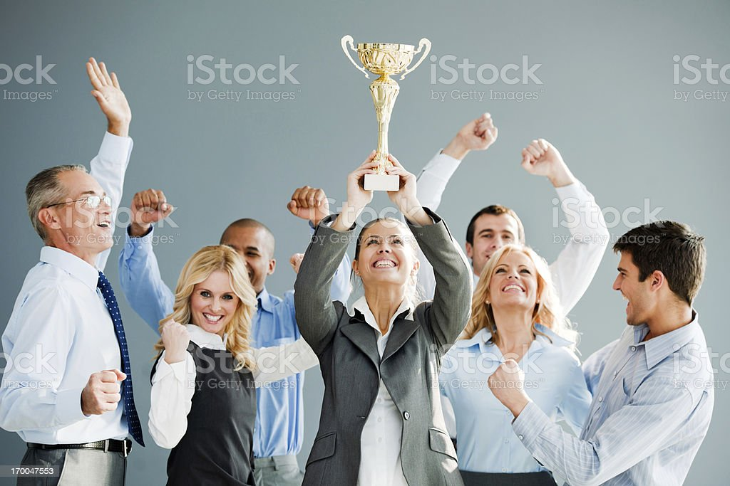 Cheerful group of businesspeople winning the cup. stock photo
