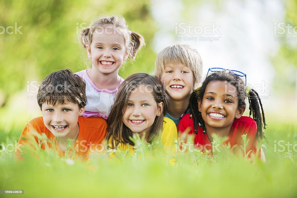 Cheerful group of children lying in the park. royalty-free stock photo