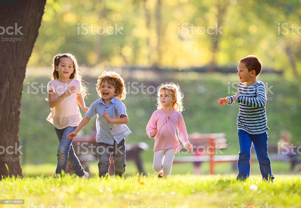 Cheerful group of children running in the park. stock photo