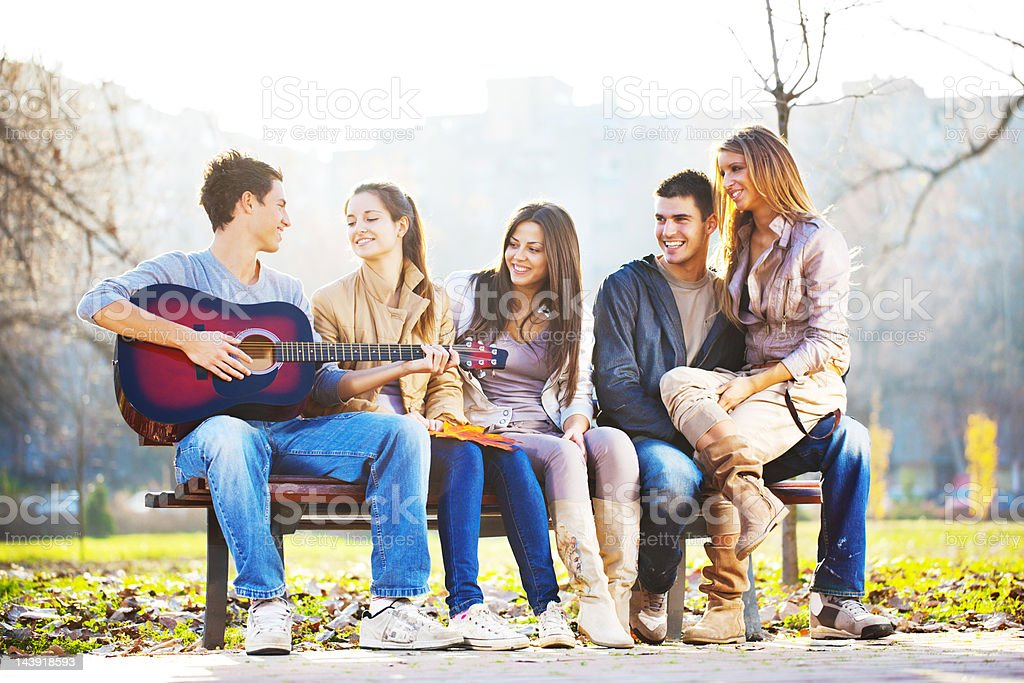Cheerful group of friend enjoying in the guitar sound. royalty-free stock photo