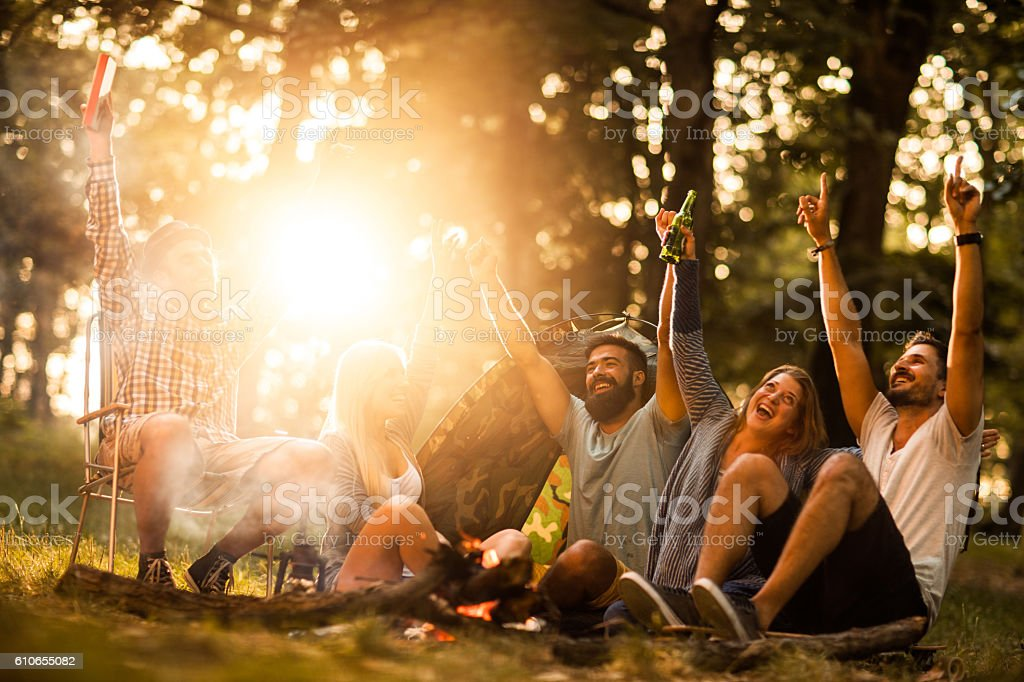 Cheerful group of friends having fun on camping in nature. stock photo