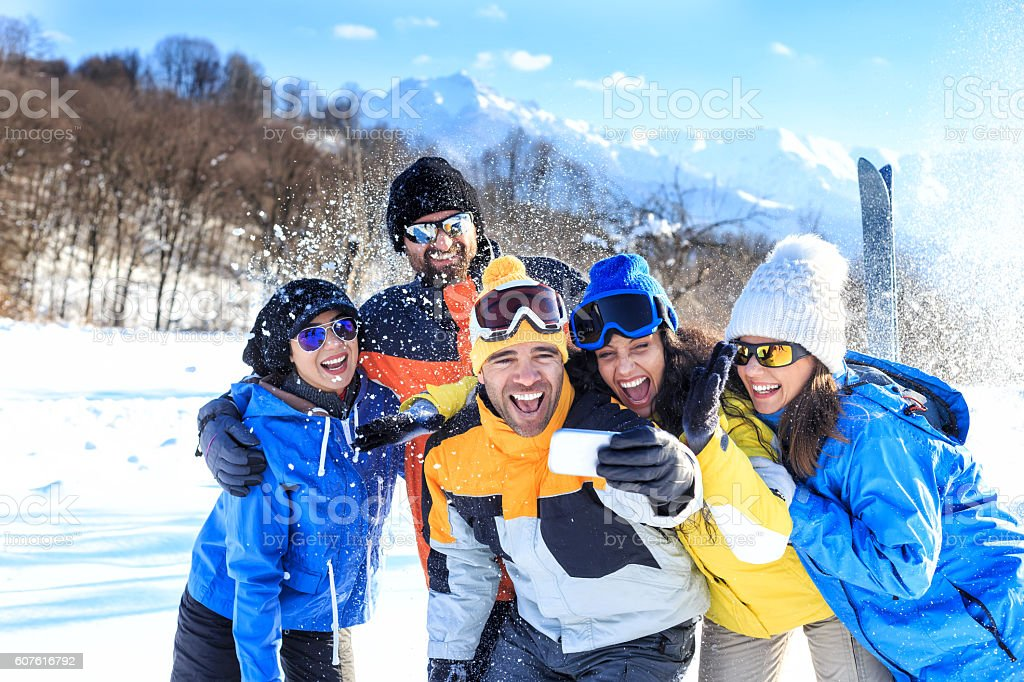 Cheerful group of friends making selfie in the snow mountain stock photo