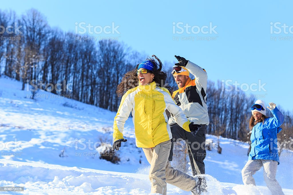 Cheerful group of friends running and jumping in snow mountain stock photo