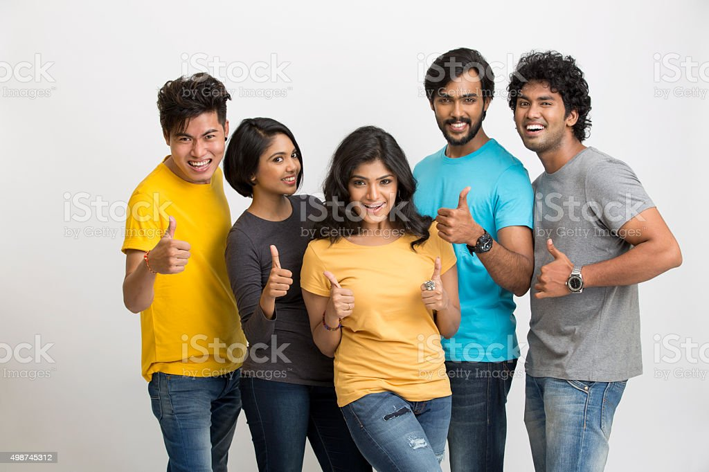 Cheerful group of Indian young friends showing thumbs up stock photo