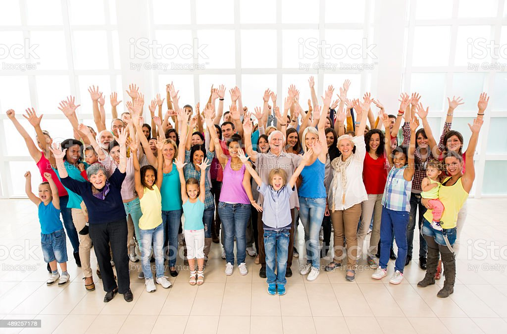 Cheerful group of people with arms raised looking at camera. stock photo