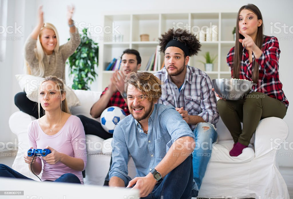 Cheerful Group Of Young Friends Playing Video Games stock photo