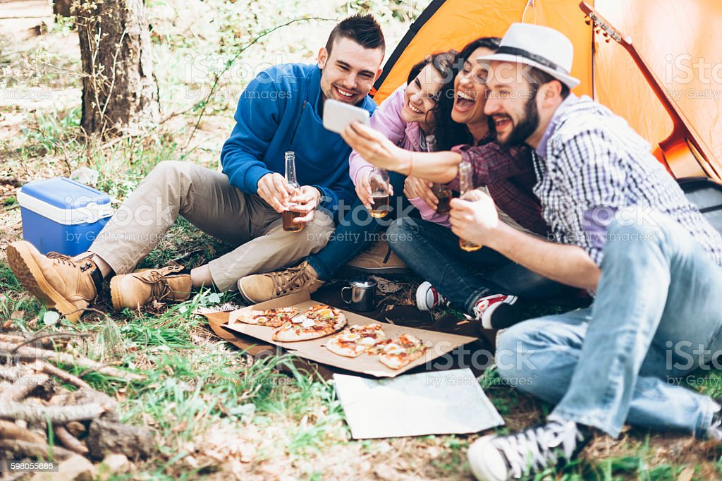 Cheerful group of young people amking selfie in the forest stock photo