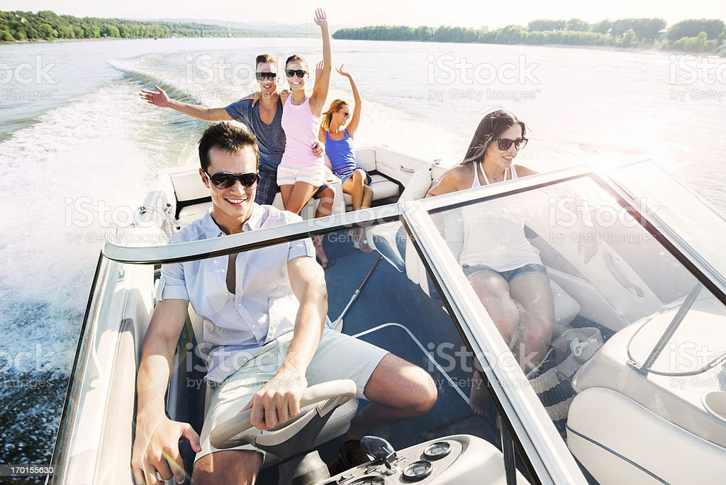 Cheerful group of young people enjoying in speedboat ride. stock photo