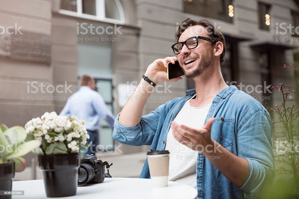 Cheerful handsome man speaking on the cellphone stock photo