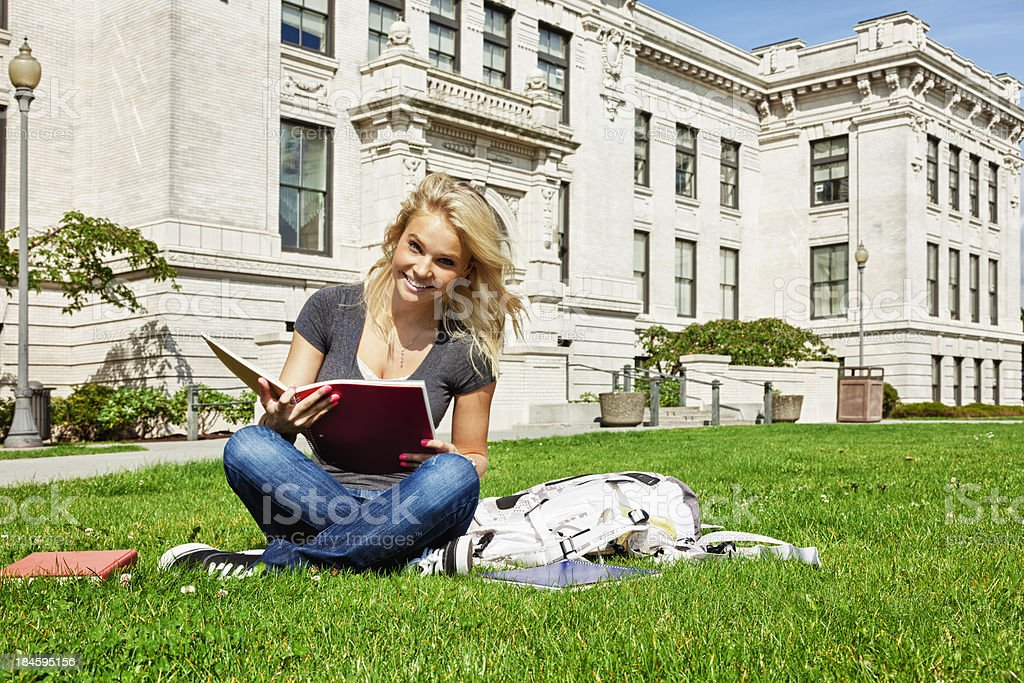 Cheerful Highschool Student Sitting on Grass in Front of School royalty-free stock photo